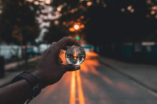 Imagen de una mano que mira la realidad a través de una lente