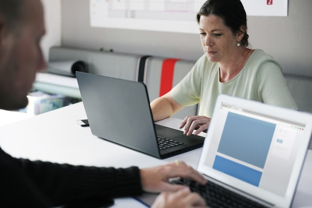 mujer y hombre trabajando en portatiles