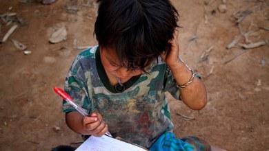Niño del tercer mundo con una pluma y un portátil